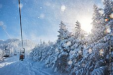 Photo of people riding chairlift on snowy day at Smugglers Notch, VErmont