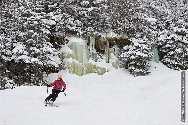 Photo of a skier turning in front of a frozen waterfall