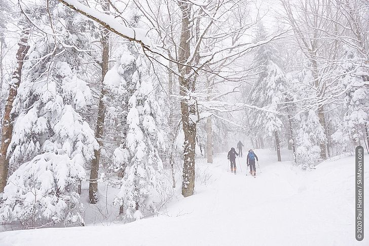 Photo of three skiers climbing a ski trail in fog