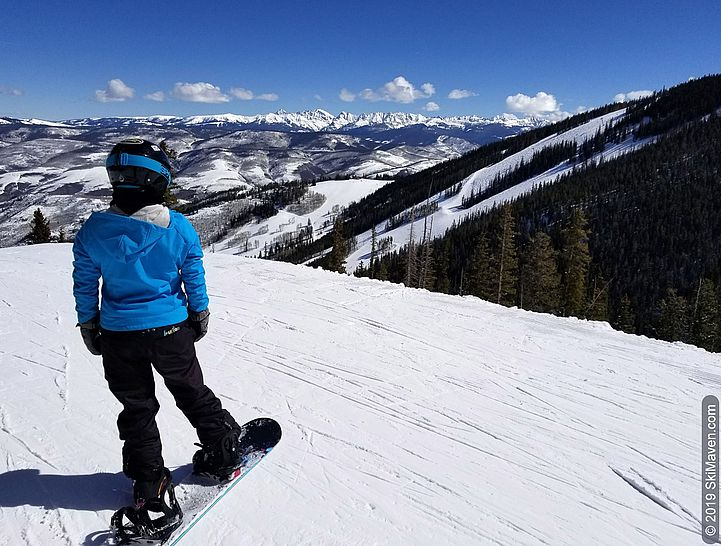Snowboarder admires mountain views from Grouse Mountain at Beaver Creek, Colorado