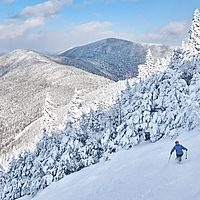 Photo of a skier on a snowy trail with a wintry view at Smugglers Notch, Vermont