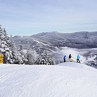 Photo of skiers on snowmaking whales on the Upper Hayride expert run