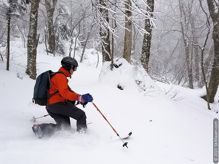Photo of skier making a telemark turn and throwing snow