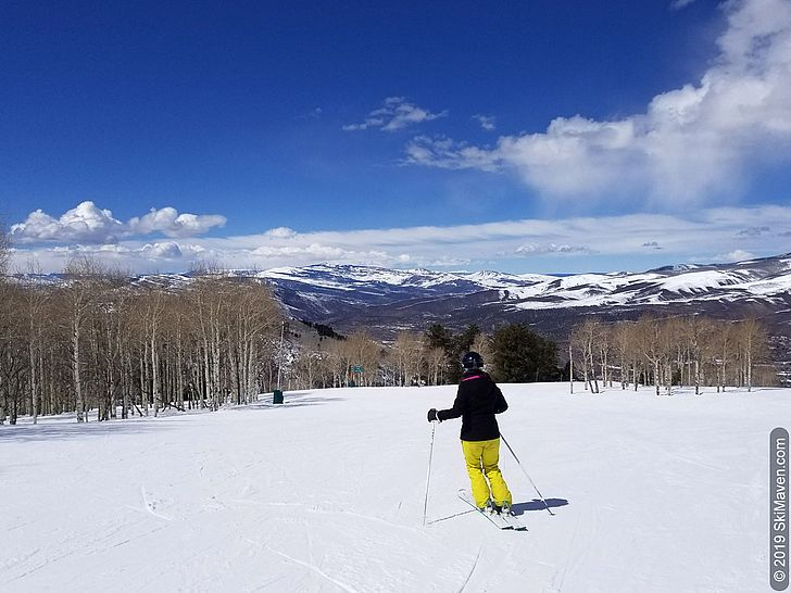 Skier makes turns at Arrowhead with aspen trees and mountains in view