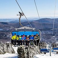 Image of blue bubble chairlift with skiers on it at Mount Snow in Vermont.